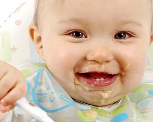Bebê-com-papinha-na-boca-sorrindo