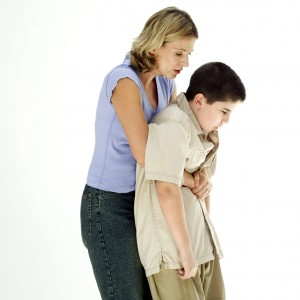 Woman Performing the Heimlich Maneuver on a Boy (10-12)
