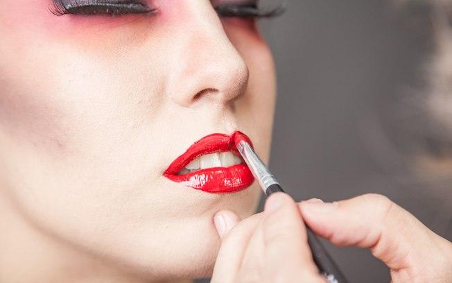 Para dar vida aos lábios, aplique um gloss vermelho por cima do batom