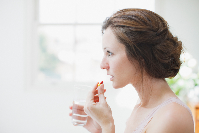 Mulher consumindo uma pílula de quitosana.