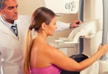 Mulher fazendo o exame de mamografia bilateral.