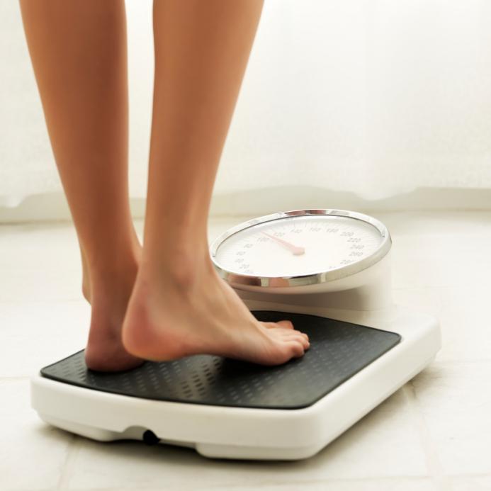 Mulher observando o ganho de peso devido a Síndrome X.