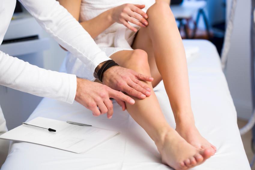 Médico examinando paciente com fraqueza nas pernas