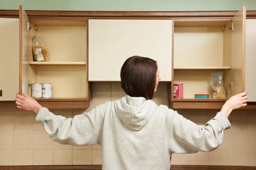 Mulher verificando o porta mantimentos da família.
