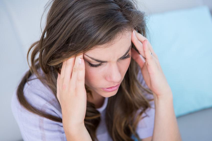 Mulher doente que sofre de dor de cabeça em casa na sala de estar