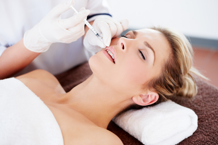 beautiful woman having botox injection in her lips
