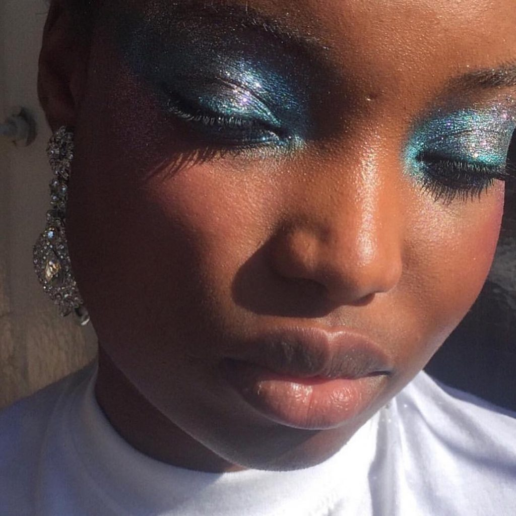 Mulher negra aparece usando maquiagem brilhante nos olhos.